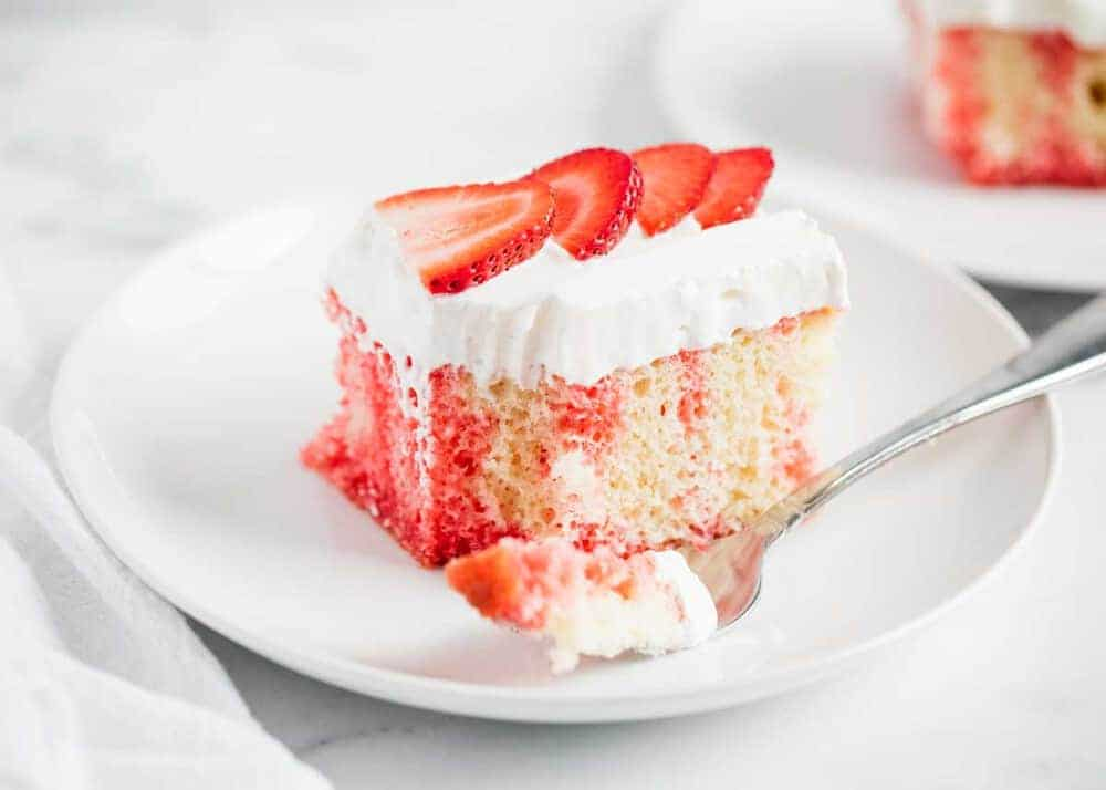strawberry poke cake on a white plate