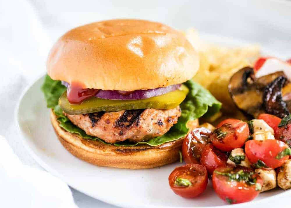 turkey burger on a white plate with salad