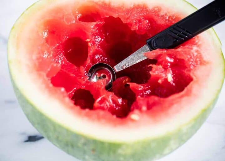 watermelon being scooped out with melon baller