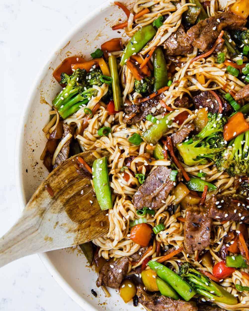 beef ramen noodles in pan with wooden spoon