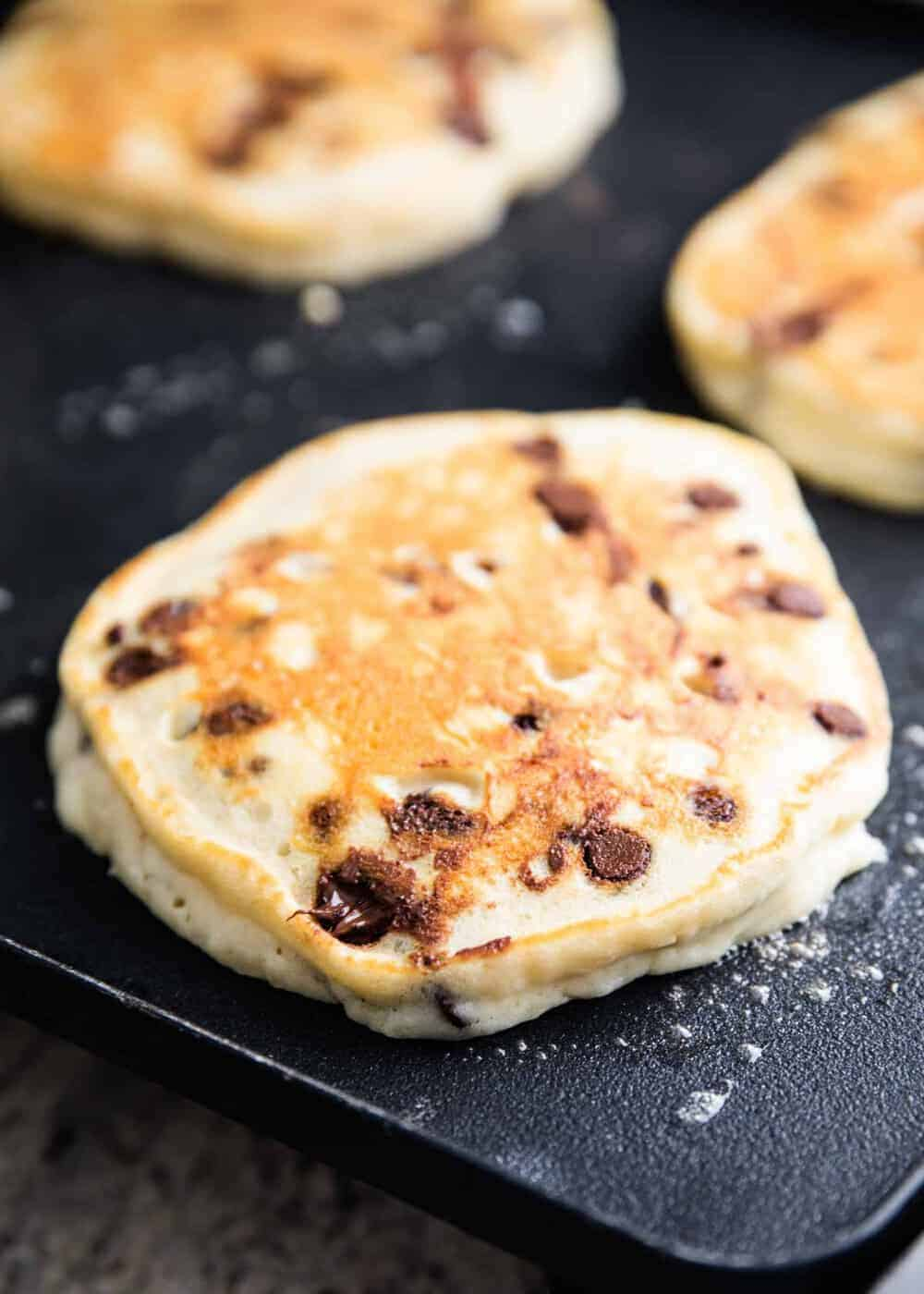chocolate chip pancakes on a griddle