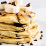 stack of chocolate chip pancakes with sliced bananas and syrup on top