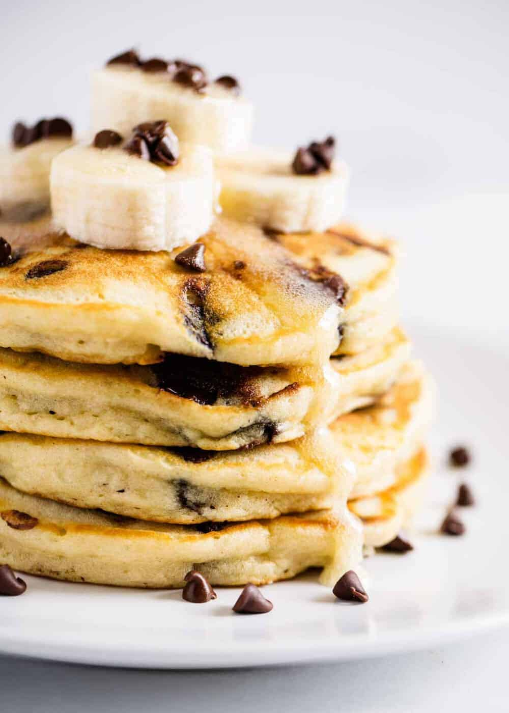 stack of chocolate chip pancakes topped with sliced bananas, chocolate chips and syrup
