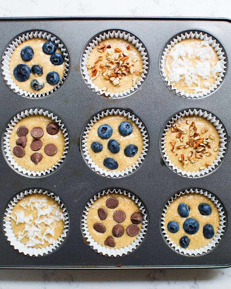 oatmeal muffin batter in muffin tin with different toppings sprinkled on