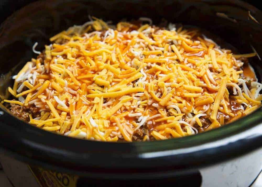 taco lasagna in the slow cooker topped with shredded cheese