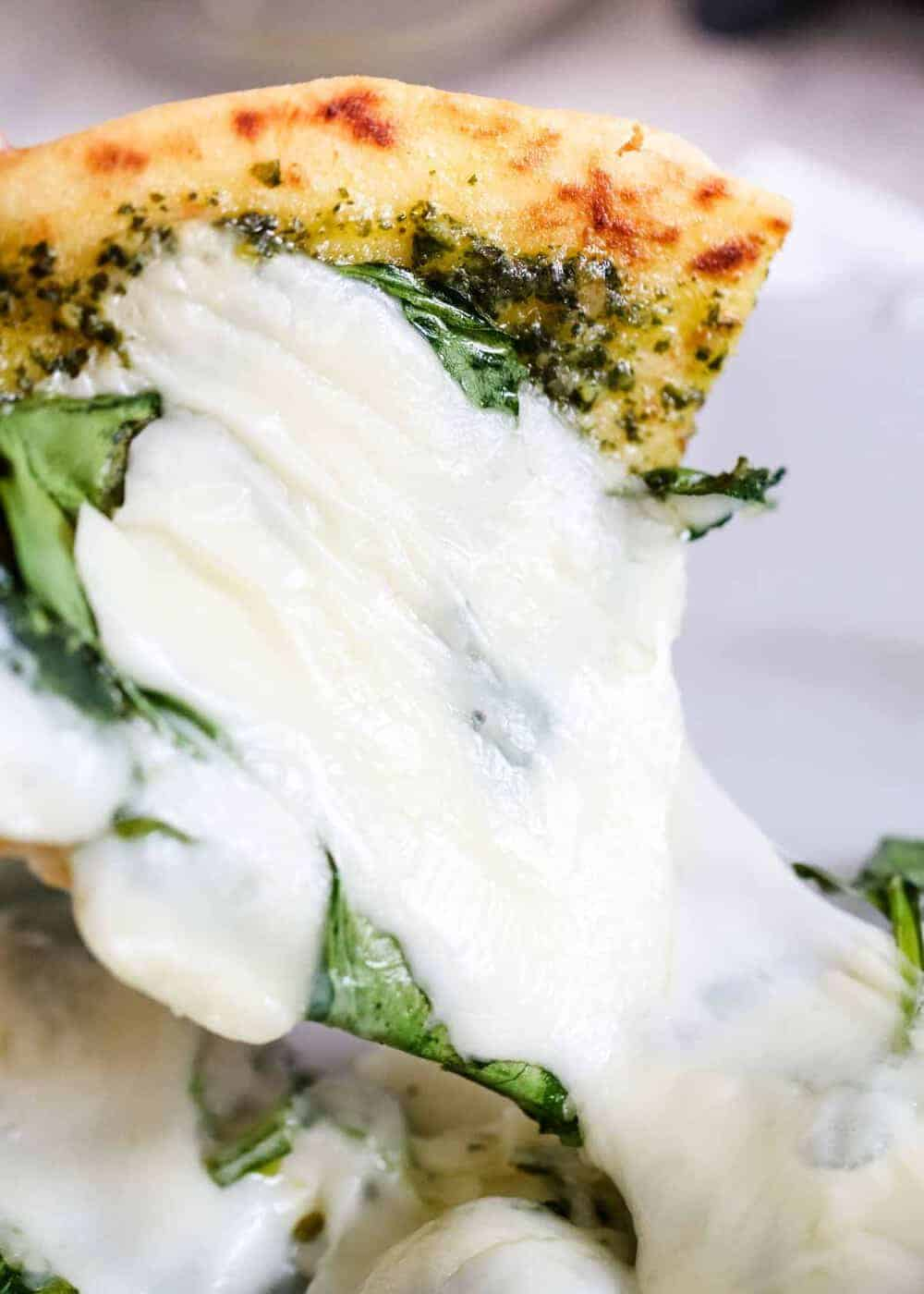 slice of pesto pizza with melted cheese