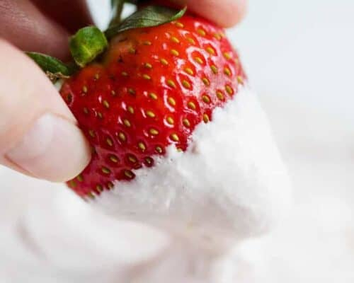 dipping a fresh strawberry into strawberry fruit dip