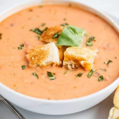 bowl of tomato soup with grilled cheese croutons and fresh basil on top
