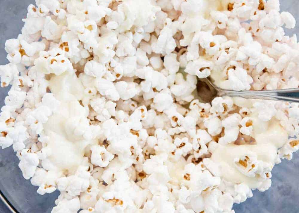 mixing together popcorn and white chocolate with a fork