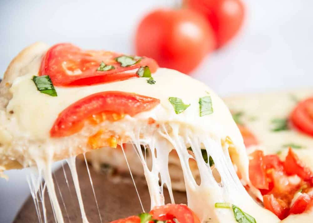 slice of white pizza with tomatoes and basil
