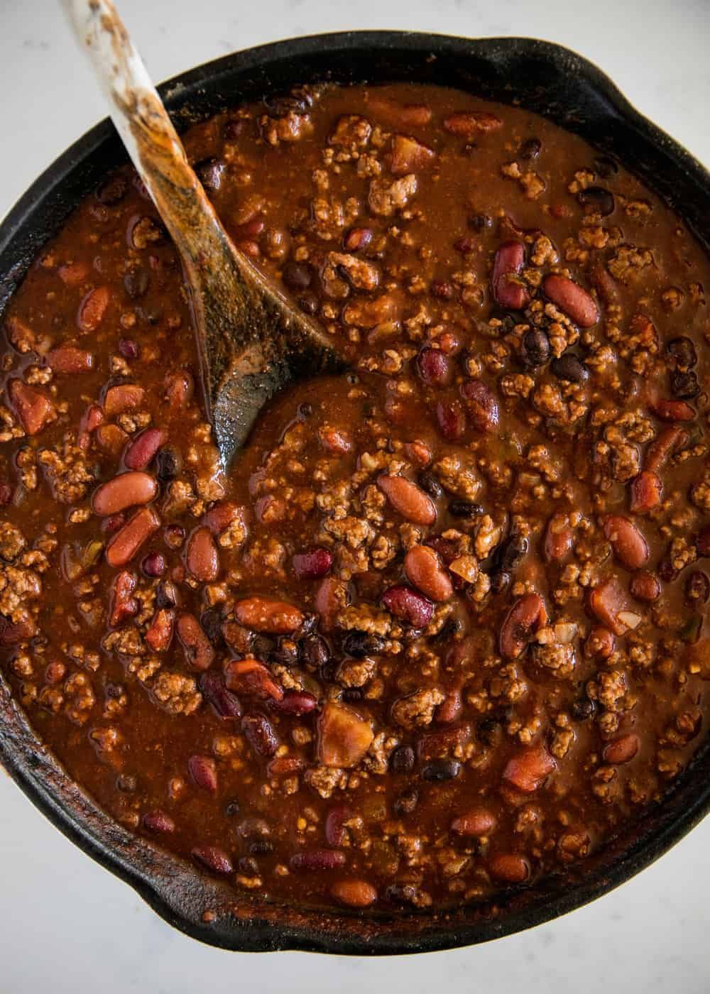 beef chili in a cast iron skillet with a wooden spoon