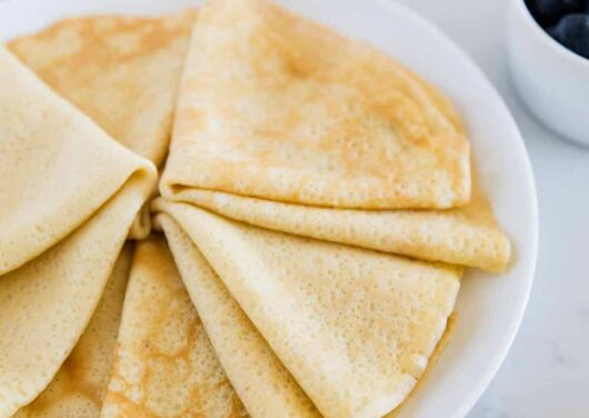 folded crepes on a white plate
