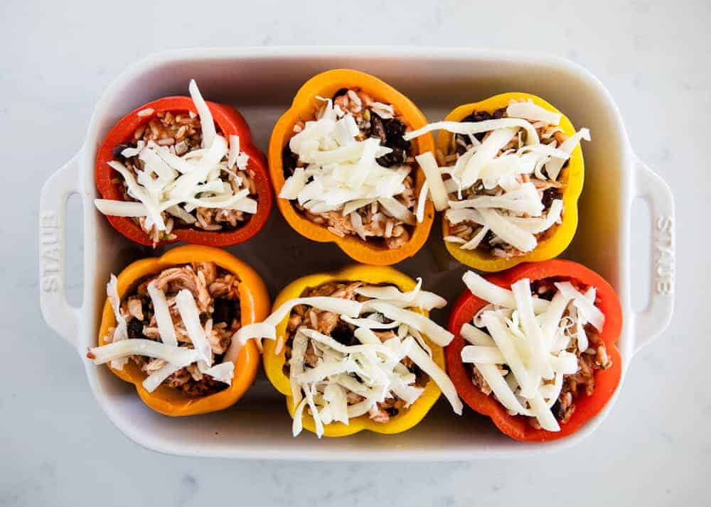 chicken stuffed bell peppers in a baking dish with shredded cheese on top