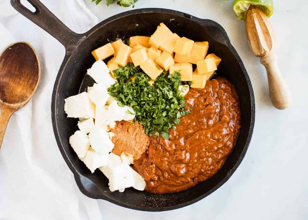 ingredients for chili queso dip in a cast iron skillet