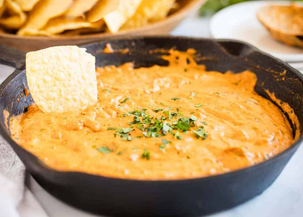 dipping a chip into chili cheese dip in a cast iron skillet