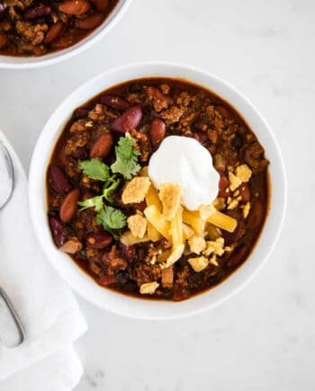 bowl of homemade chili topped with sour cream, cheese, cilantro and crushed chips