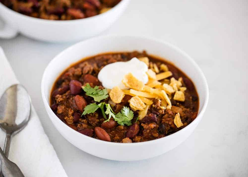 bowl of homemade chili topped with shredded cheese, sour cream and cilantro