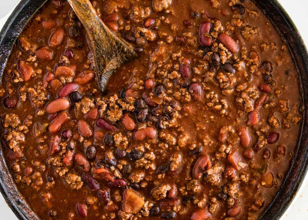 making homemade chili in a cast iron skillet with a wooden spoon
