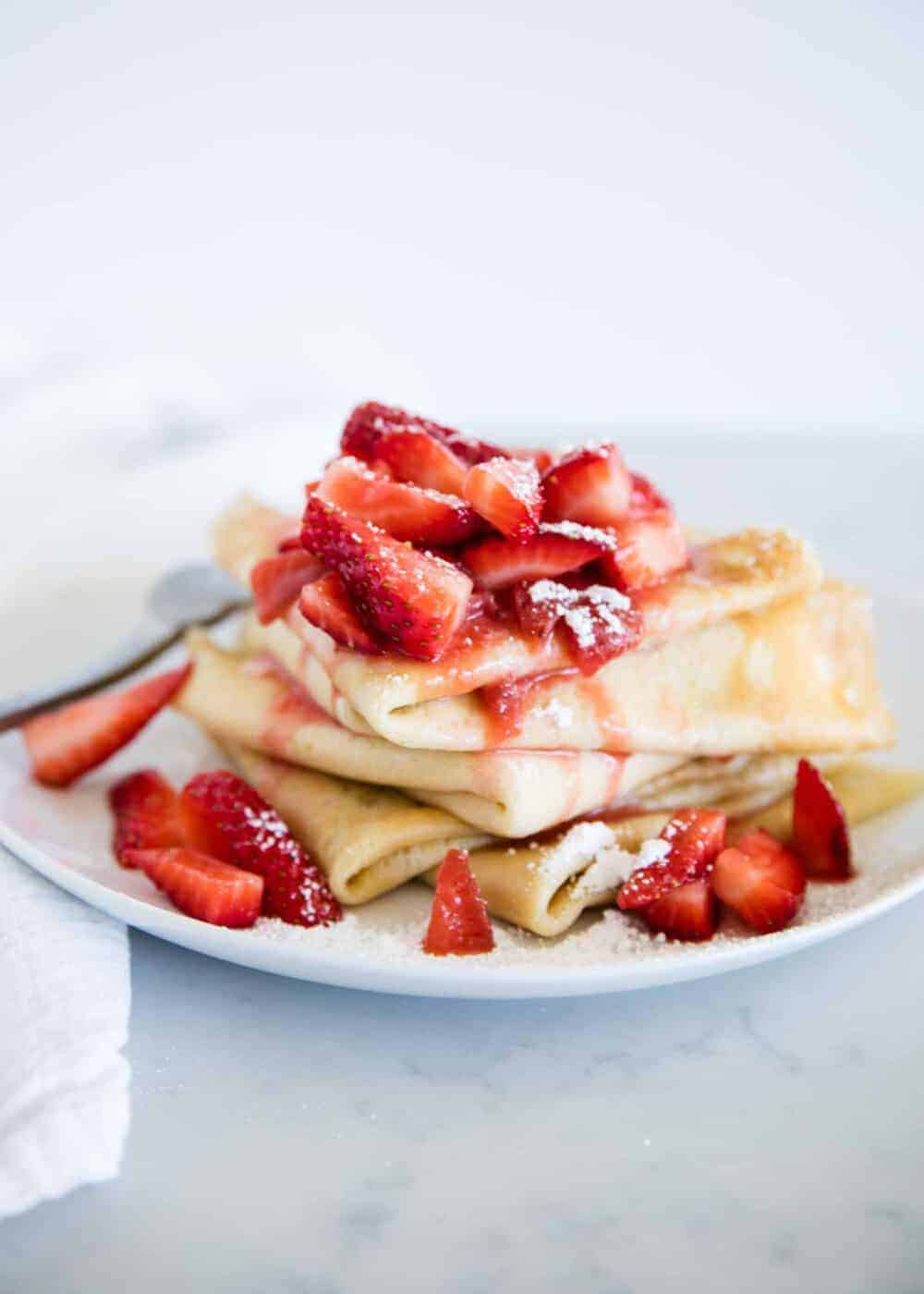 stack of crepes on a white plate topped with strawberry sauce