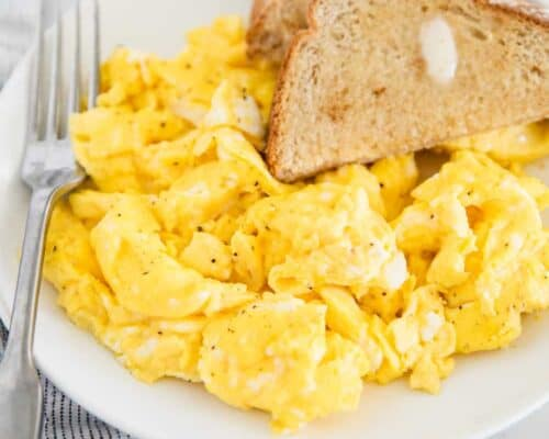 scrambled eggs on white plate with toast
