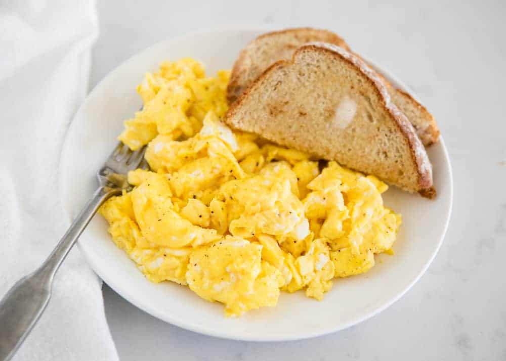 scrambled eggs with toast on a white plate