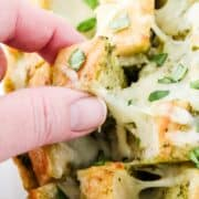 pulling out a piece of cheesy pesto bread with finger