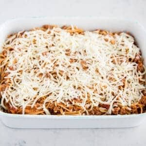 baked spaghetti being dished out of pan