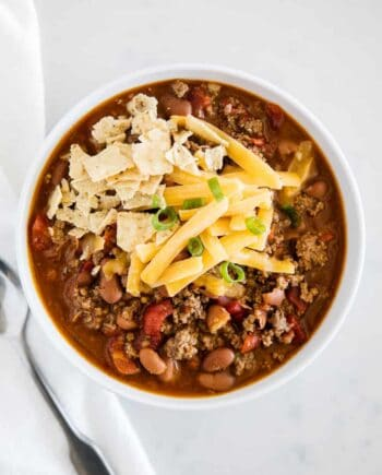 chili in a white bowl with tortilla chips and cheese