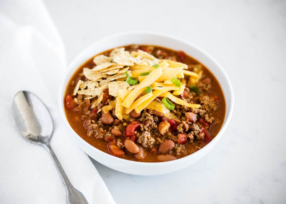 bowl of chili topped with cheese, crushed tortilla chips and green onions