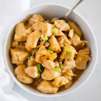 orange chicken with green onions in white bowl