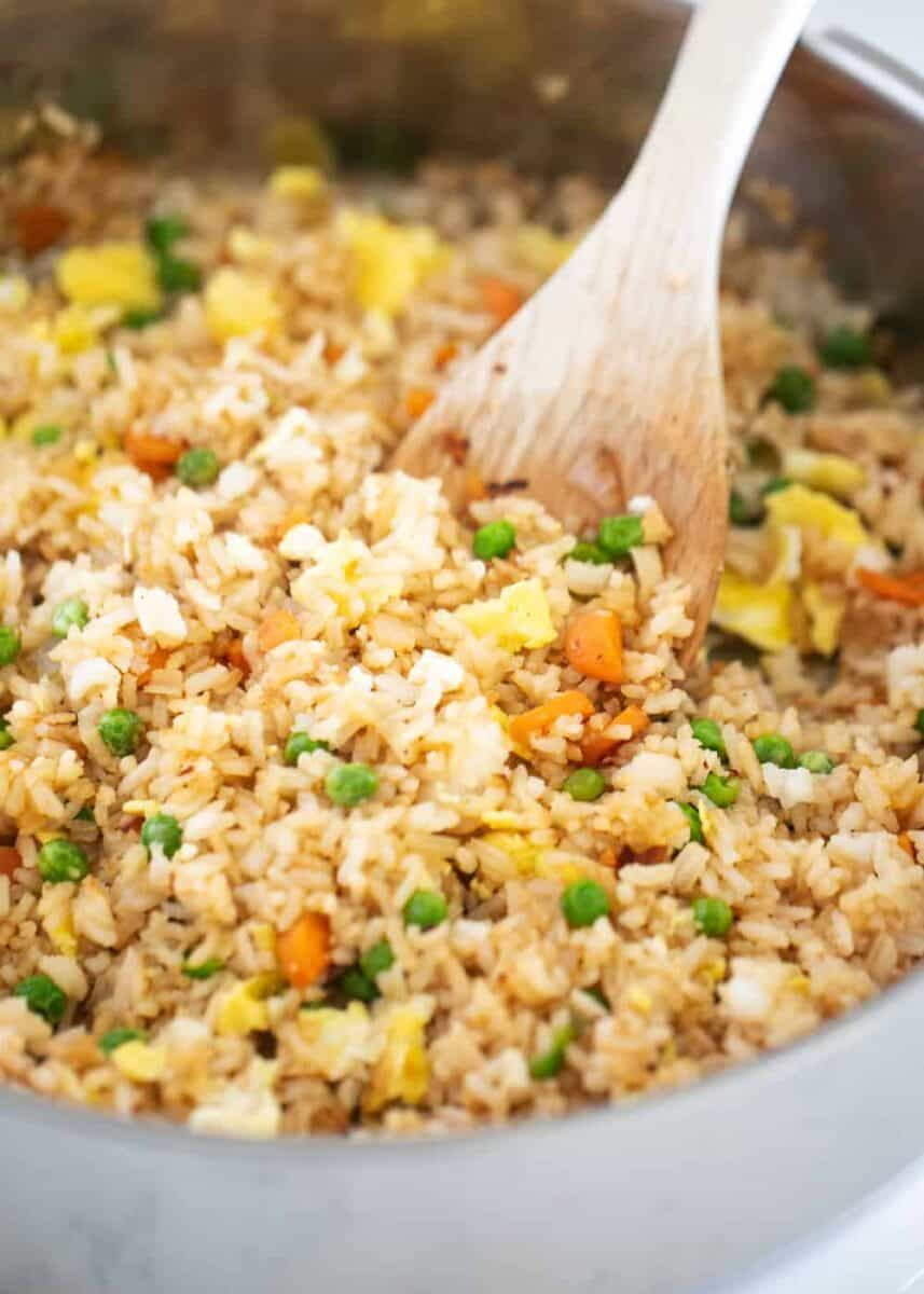 fried rice in pan with wooden spoon
