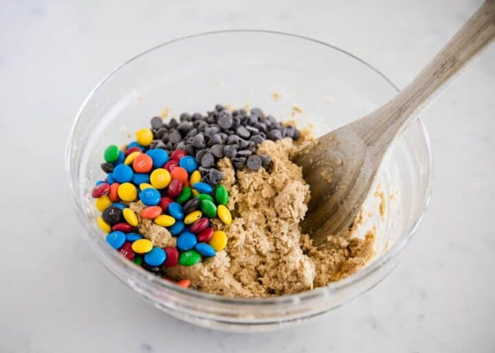 mixing monster cookie dough in glass bowl with wooden spoon