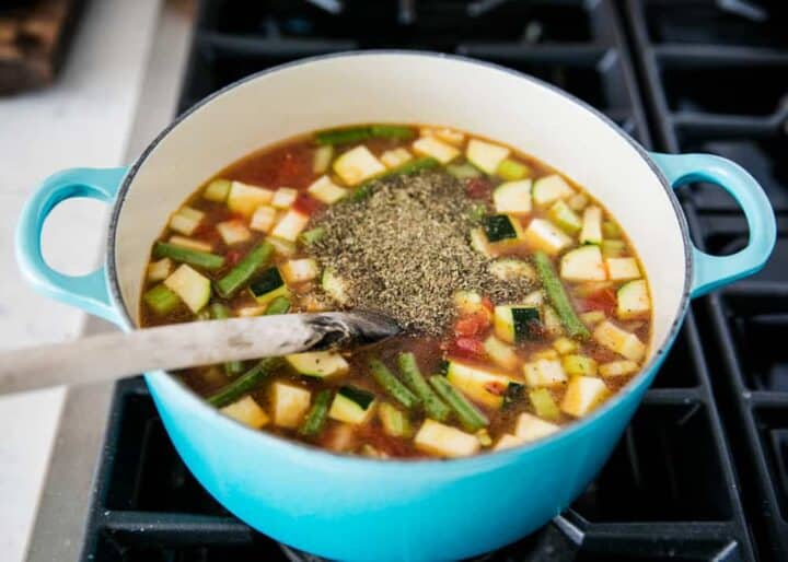 adding spices into pot of minestrone soup on the stove
