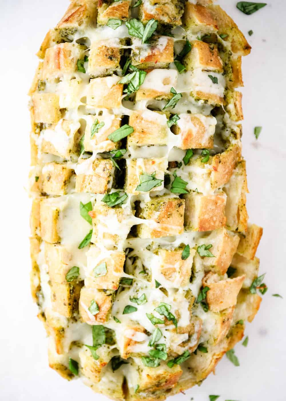 loaf of cheesy pull-apart bread with fresh basil on top