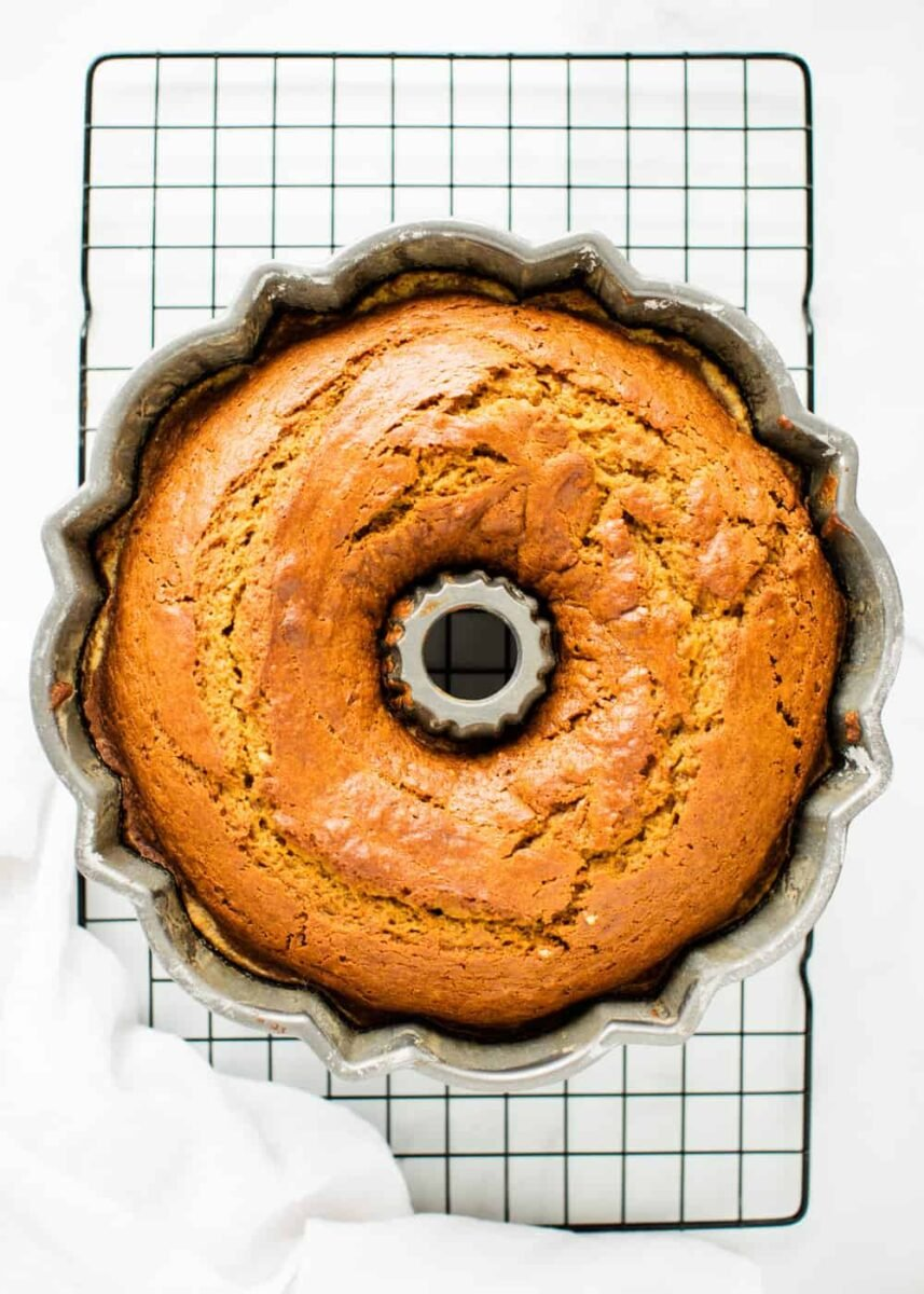 cooked pumpkin bundt cake in pan sitting on a baking rack