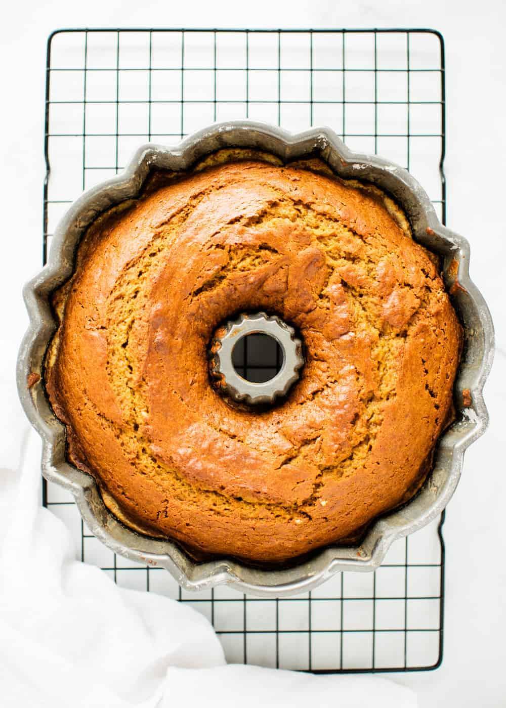 cooked pumpkin bundt cake in pan sitting on a baking rack