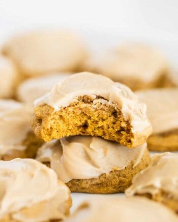 iced pumpkin cookies with a bite taken