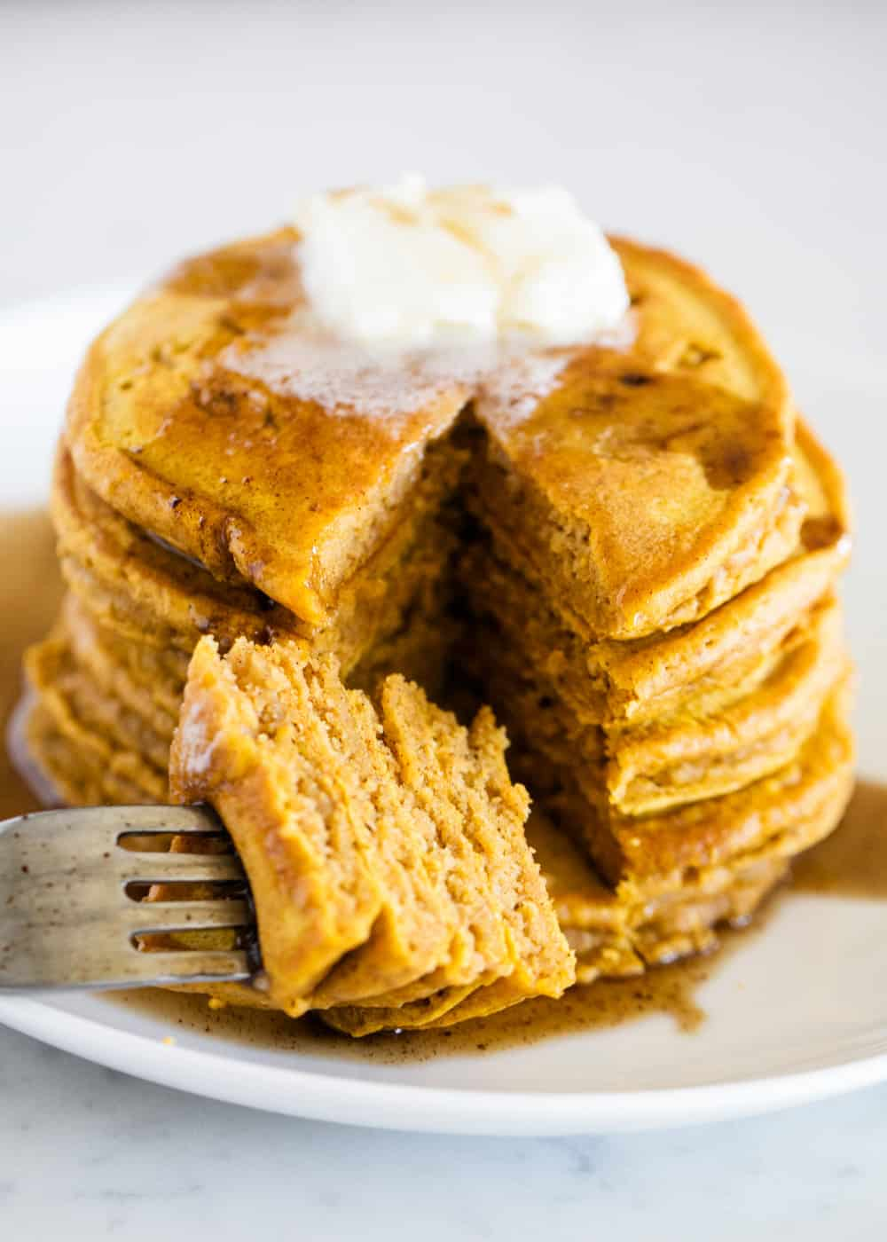 stack of pumpkin pancakes with butter and syrup