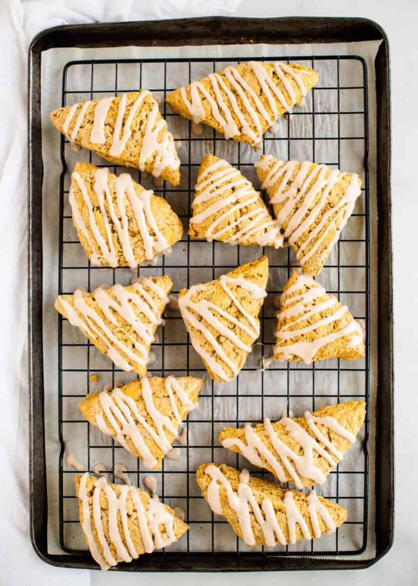 pumpkin scones on cooling rack with glaze drizzled on top