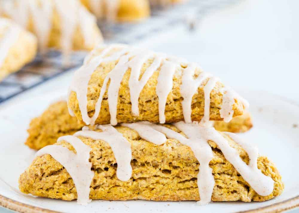 stack of two pumpkin scones with glaze drizzled on top
