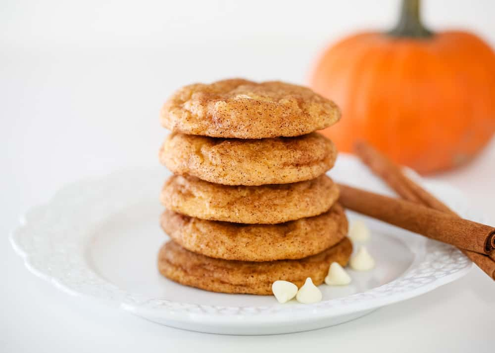 stack of pumpkin snickerdoodles on a white plate with cinnamon sticks