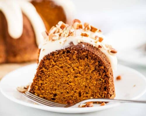 piece of pumpkin bundt cake on a white plate with a fork