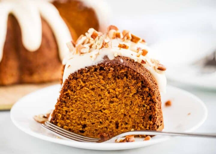 piece of pumpkin bundt cake with cream cheese frosting on a white plate