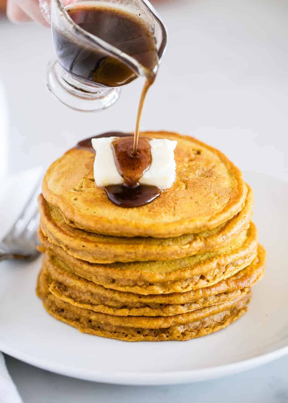 stack of pumpkin spice pancakes with butter and syrup