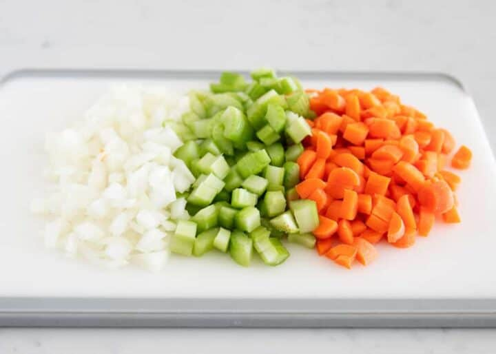 chopped onion, celery and carrots on a cutting board
