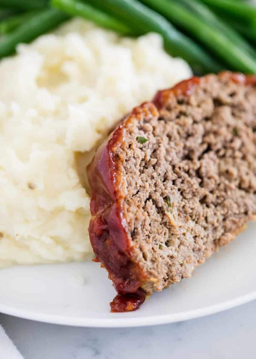 slice of meatloaf and mashed potatoes on white plate