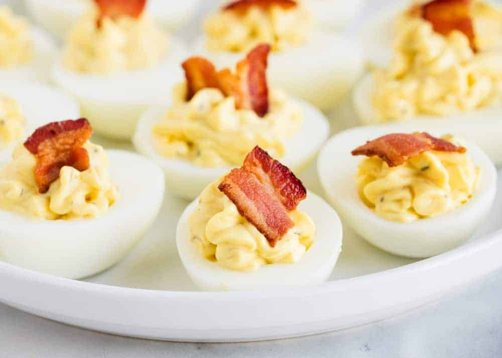 deviled eggs with bacon on a white plate