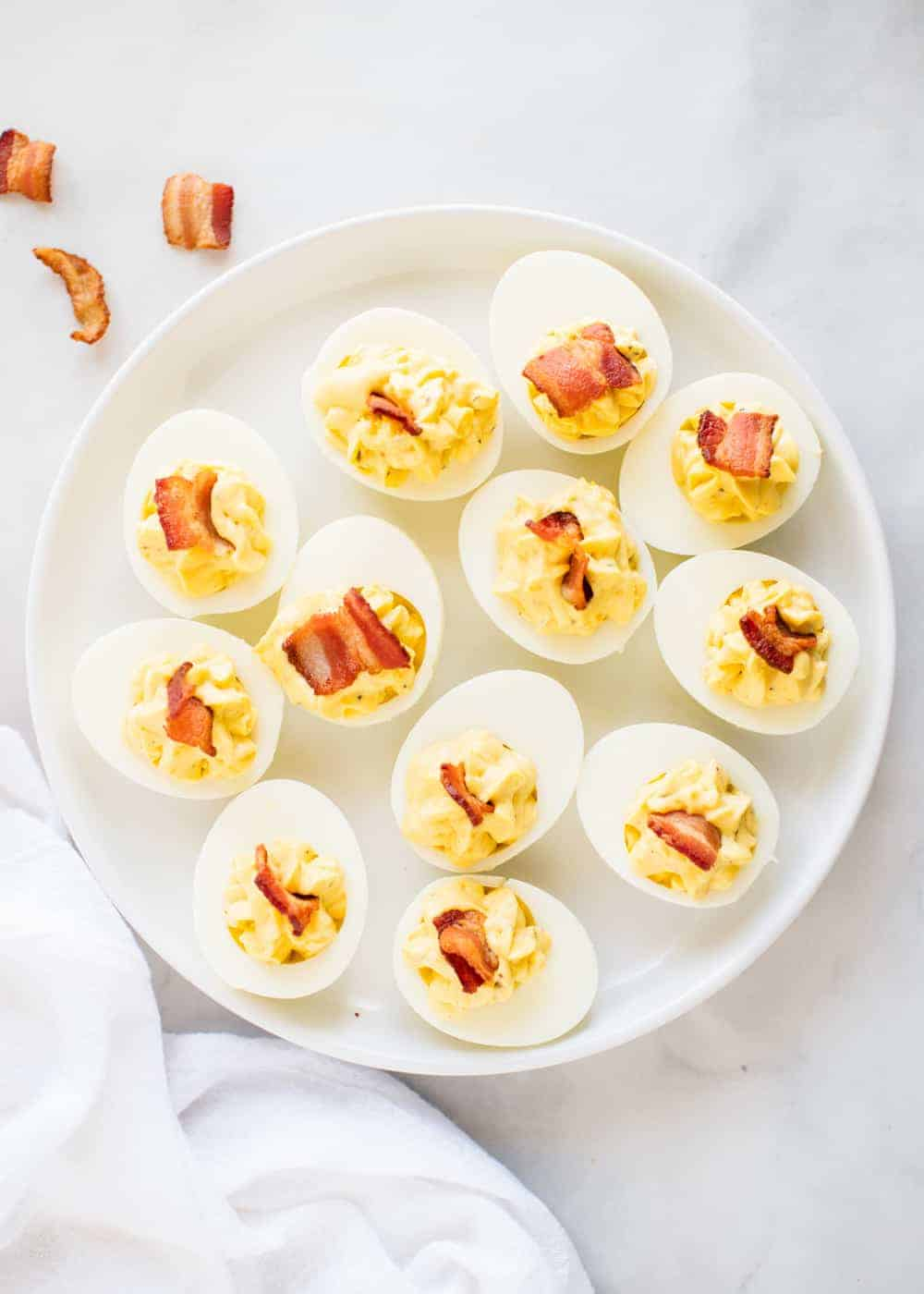 ranch deviled eggs with bacon on a white plate