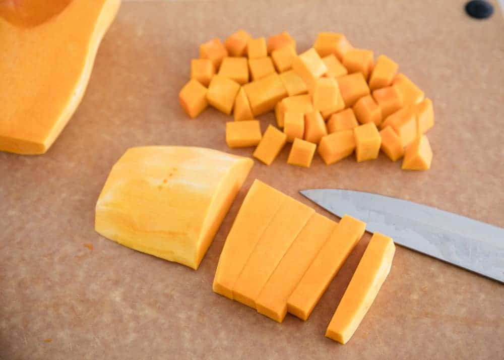 slicing butternut squash on a cutting board with a knife