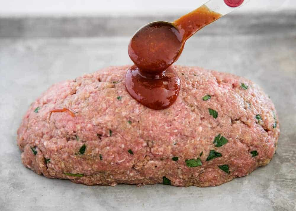 meatloaf on pan with sauce being poured over